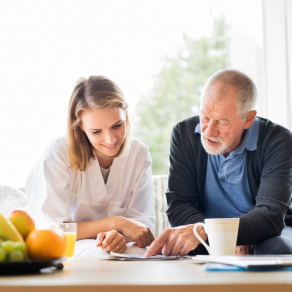 health-visitor-and-a-senior-man-with-tablet-p2qtnng